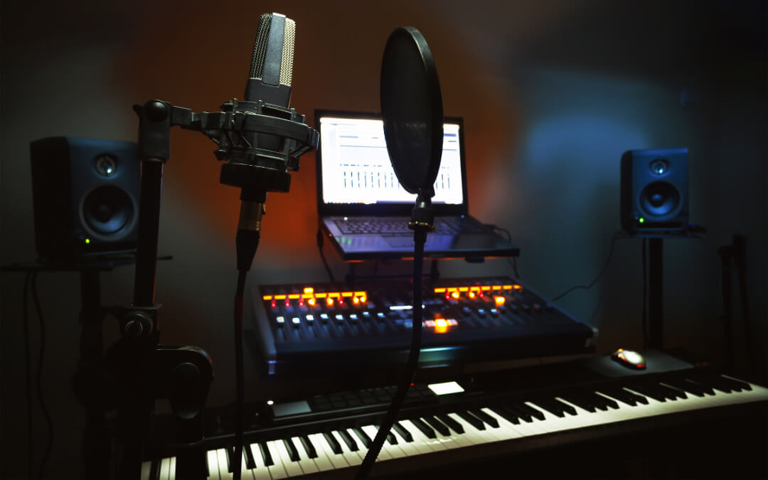 recording studio showing microphone, laptop and keyboard