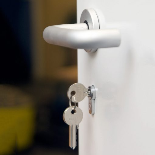 Close up of a key in the lock and a door handle