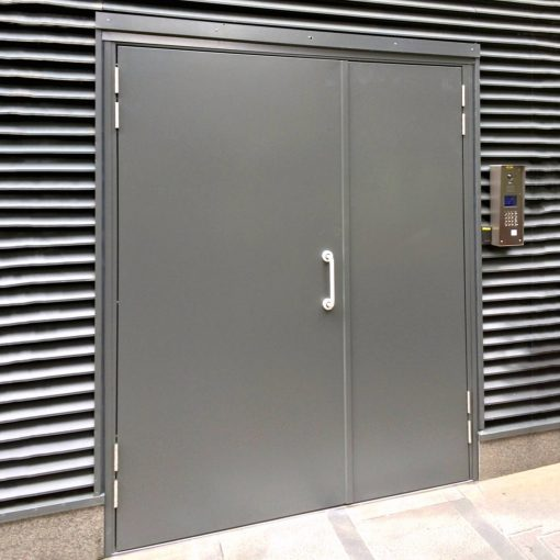 Grey double steel door installed on a building unit with D handle